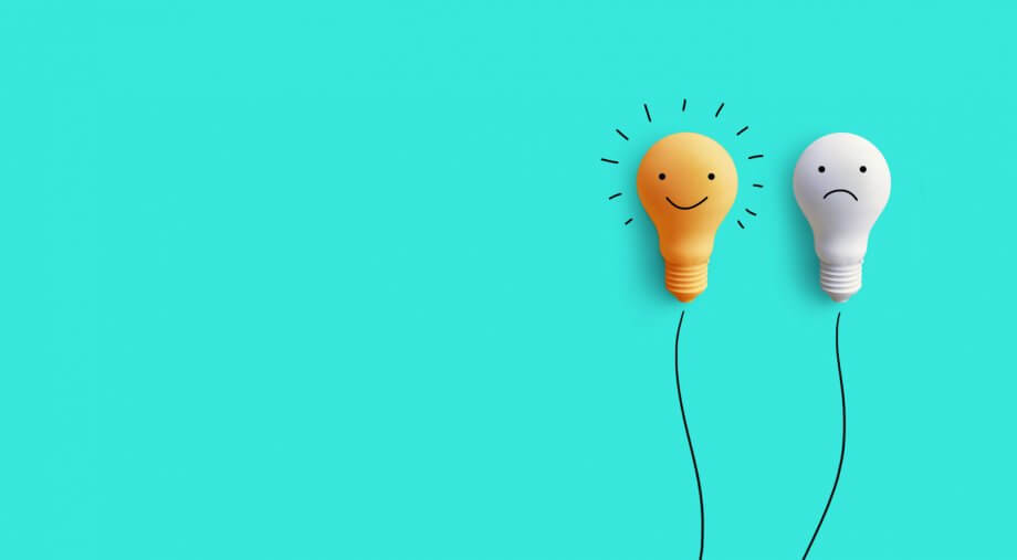 Two lightbulbs in front of a teal background. One lightbulb is smiling and yellow the other is gray and frowning.