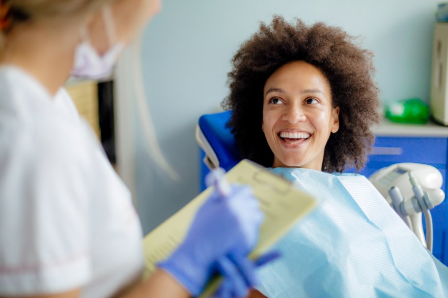 Woman smiling while sitting in chair at dentist
