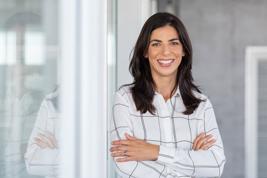 smiling woman with arms crossed standing next to glass wall