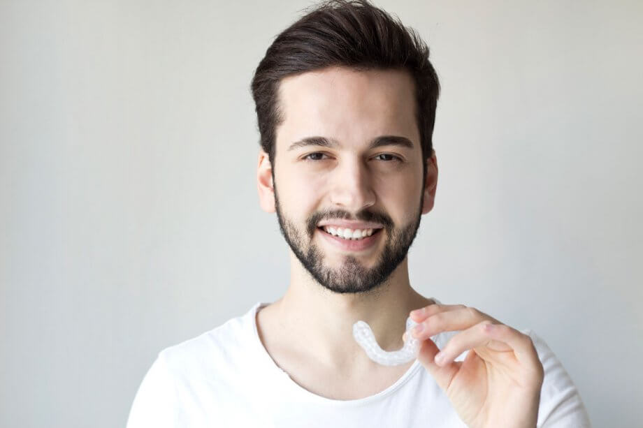 smiling man holding invisalign appliance