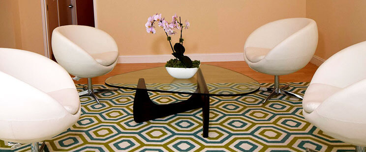 four round white chairs with glass table and geometric rug